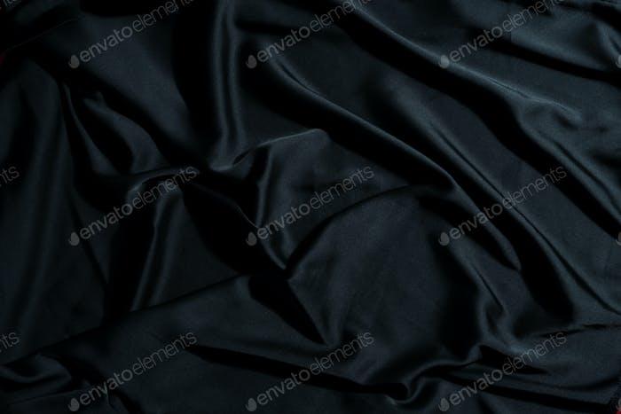 Zerknitterter Textilgewebe Hintergrund der schwarzen Farbe