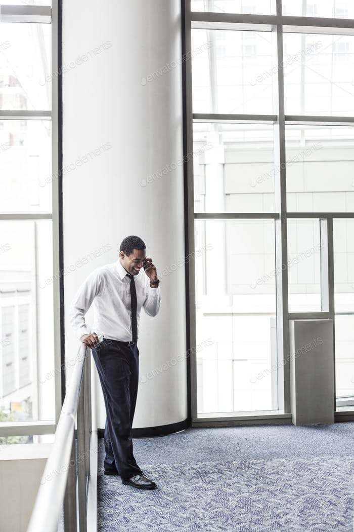 Black businessman on the phone in an office lobby.