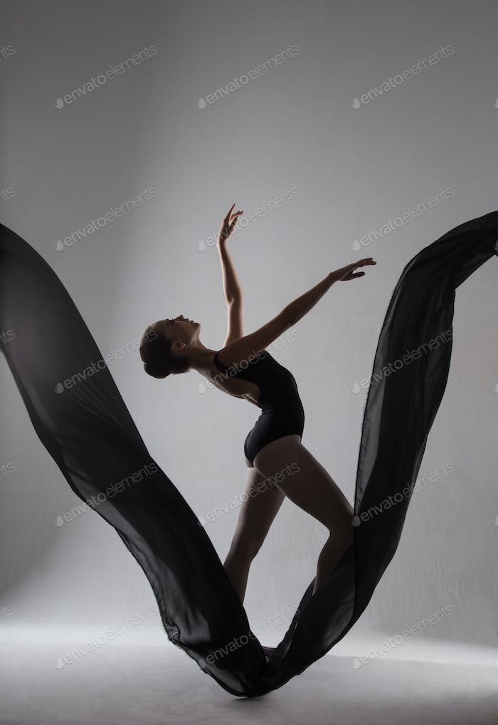 Silhouette of a ballerina dancing on a black cloth