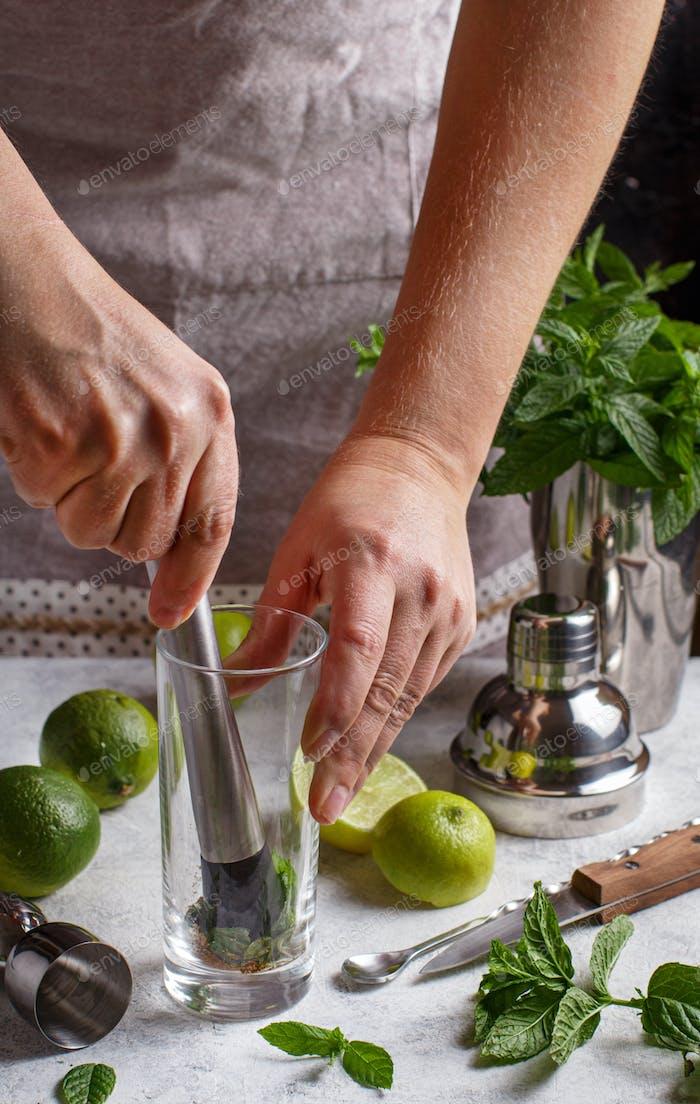 Hands making Mojito cocktail  using  barmen tools