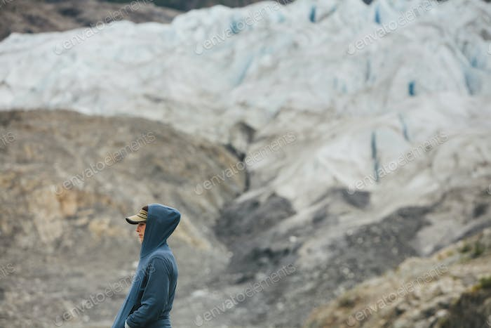 A young woman standing at the end of a glacier on a rocky shoreline in Alaska.