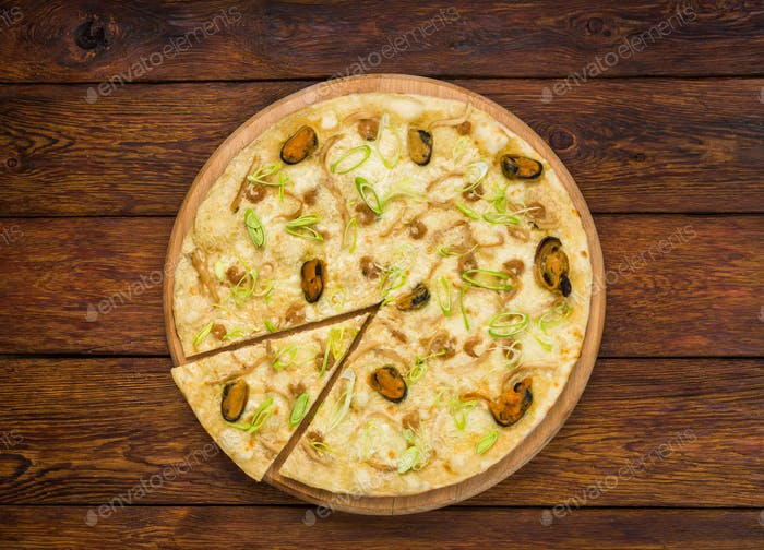 Italian seafood pizza top view at wood background