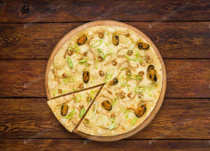 Italienische Meeresfrüchte-Pizza auf Holzhintergrund