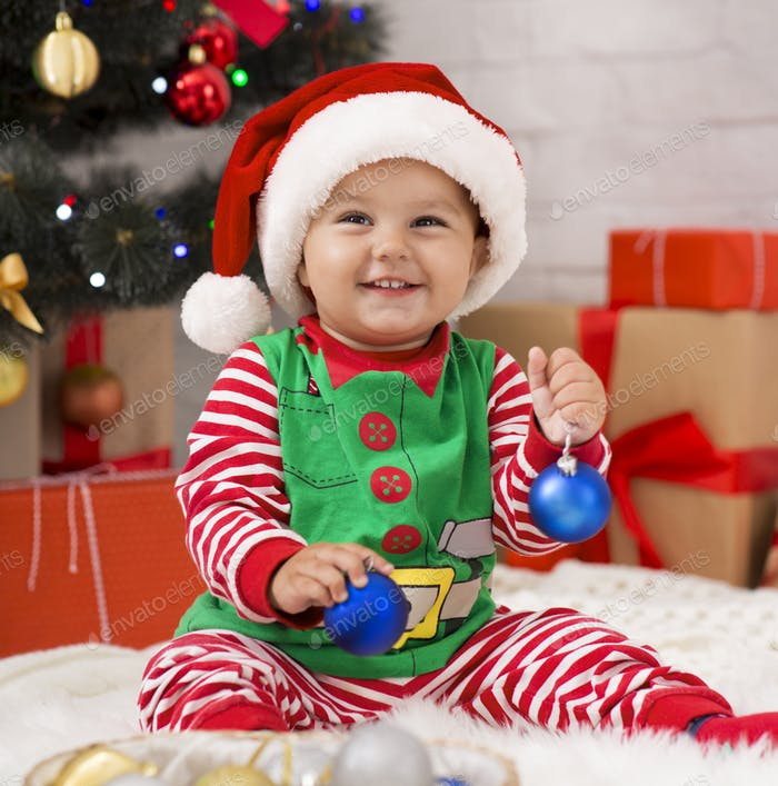 Adorable baby elf playing with blue Christmas balls