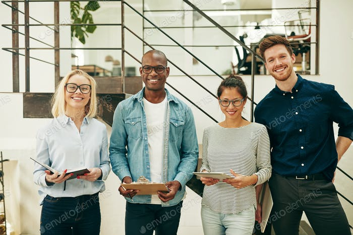 Diverse businesspeople smiling confidently while working together in an office