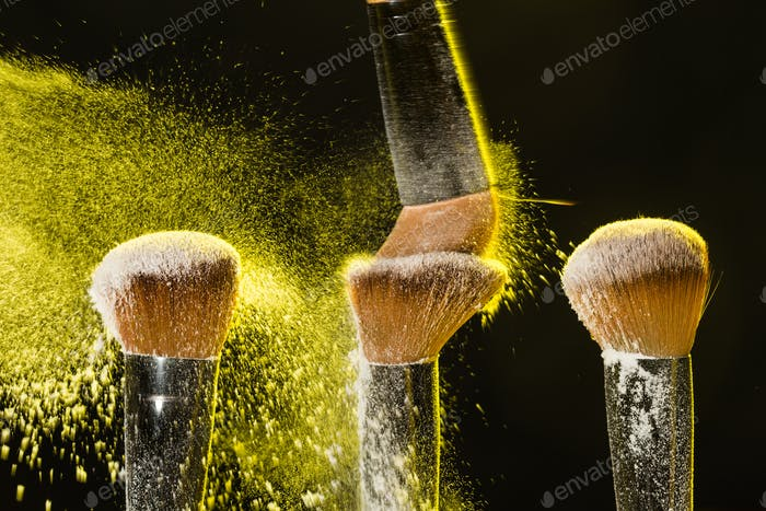 Three brushes for makeup with yellow make-up powder in motion on a black background