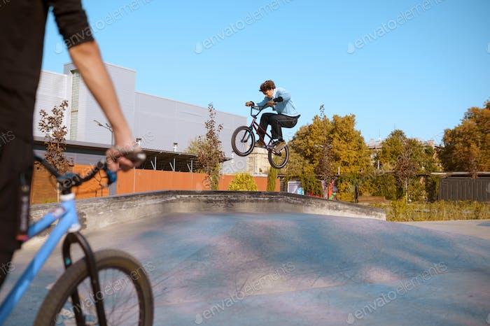 Jinete BMX, salto en acción, entrenamiento en skatepark