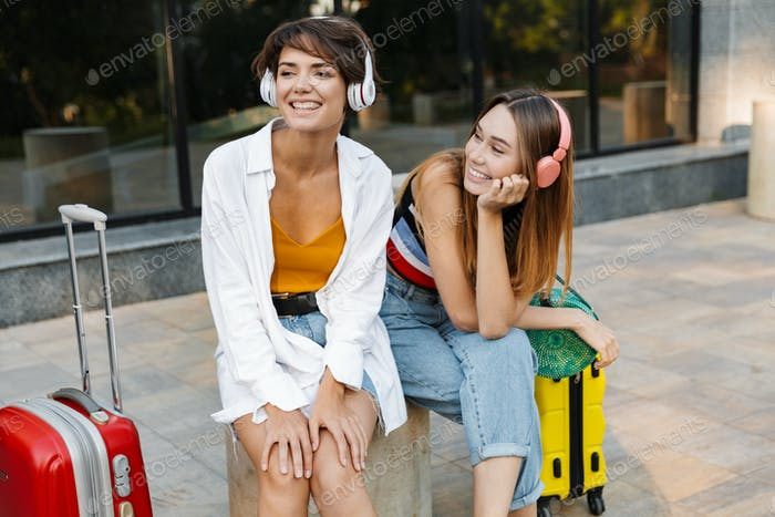 Photo of two happy beautiful women listening music in headphones