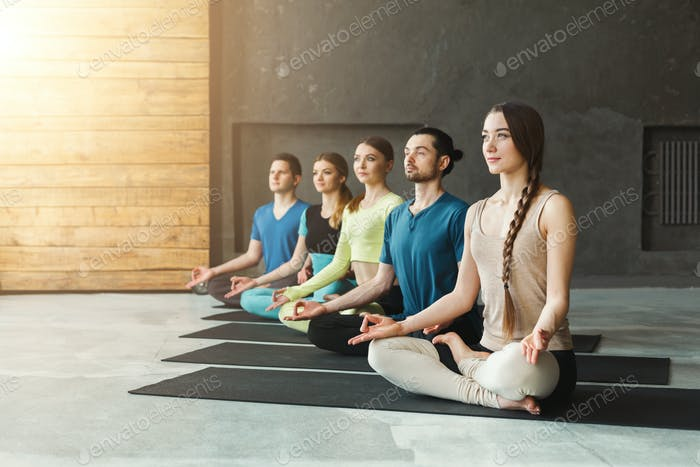 Young Women And Men In Yoga Class Relax Meditation Pose