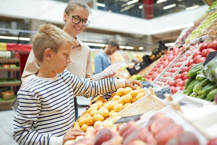 Boy Choosing Fruits in Supermarket