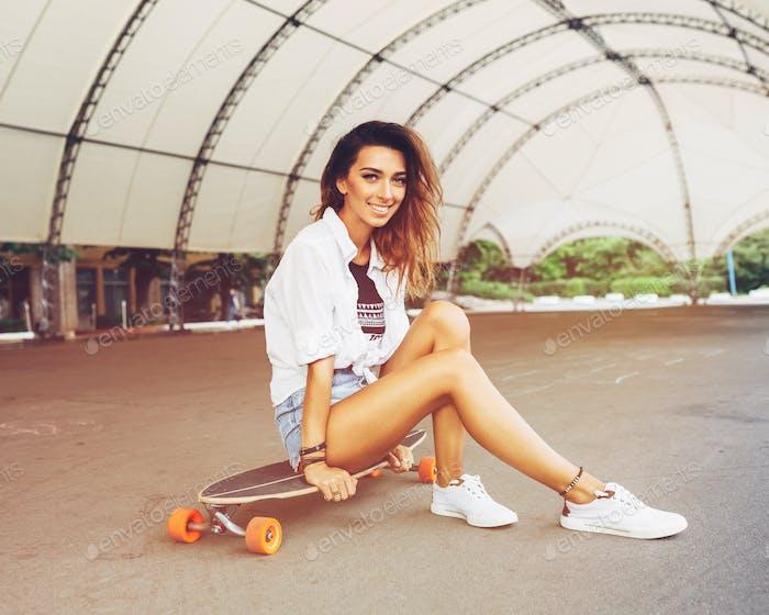 Fashion lifestyle, beautiful young woman with longboard. Lightle