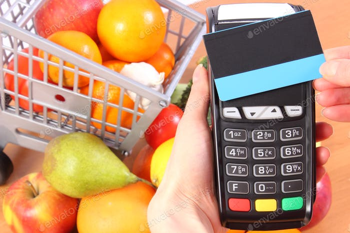 Payment terminal with contactless credit card and fruits and vegetables