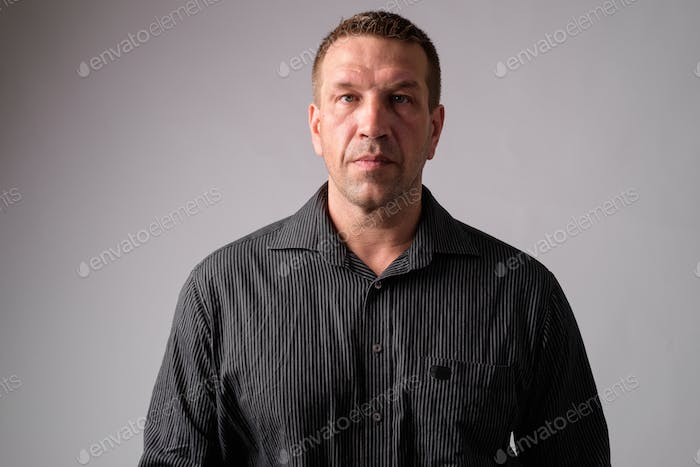 Portrait of macho mature businessman looking strong and muscular