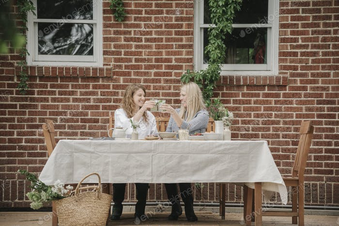 Two  women seated outside a house having a meal.