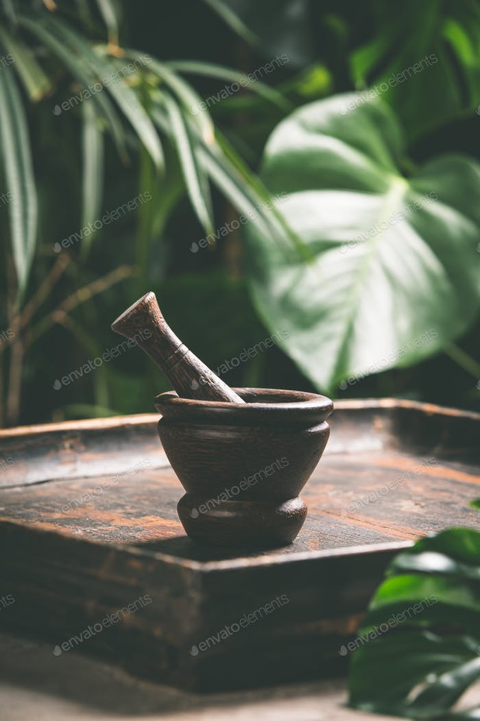 Mortar and pestle on tropical background, close up