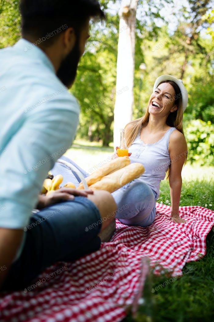 Glückliches Paar im Urlaub. Liebhaber genießen einander im Park, Picknick
