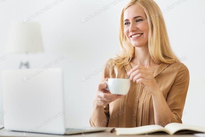 Happy entrepreneur woman drinking coffee, working on laptop