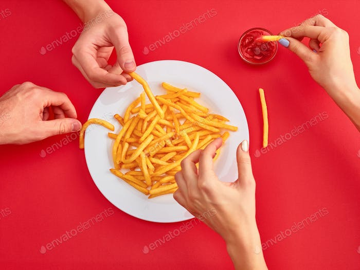 Young woman eating french fries potato with ketchup in a restaurant