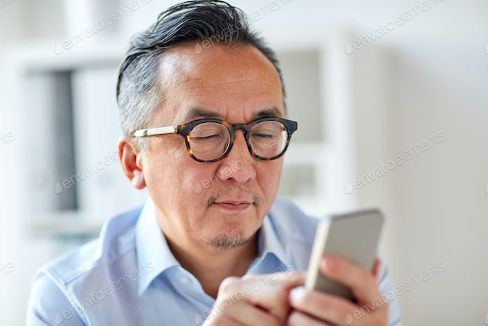businessman texting on smartphone at office