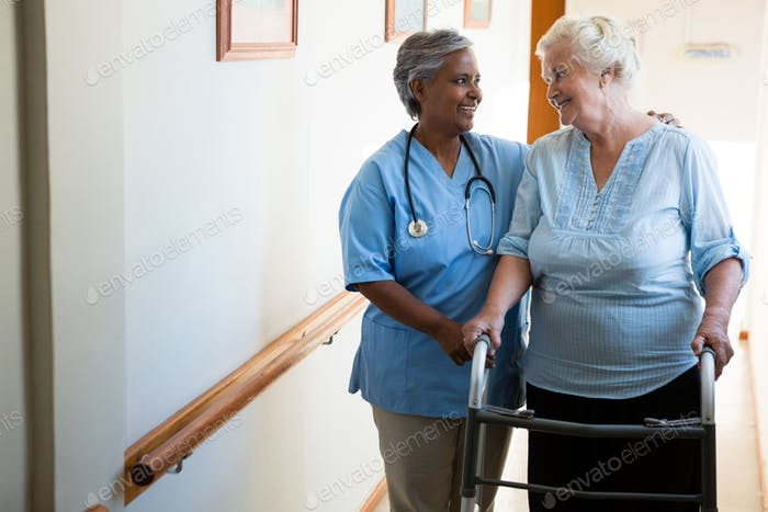 Nurse assisting patient in walking with walker at retirement home