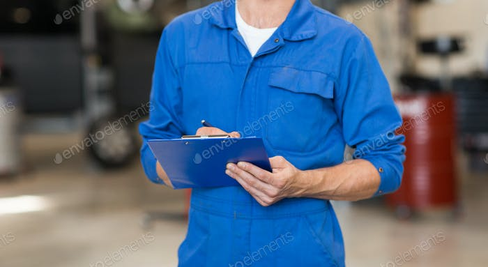 mechanic man with clipboard at car workshop