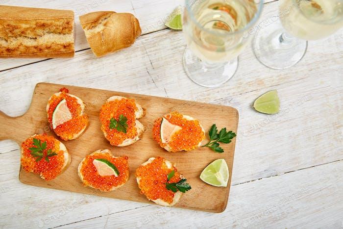 Lachsroter Kaviar in Schüssel und Sandwiches mit Holzschneidebrett