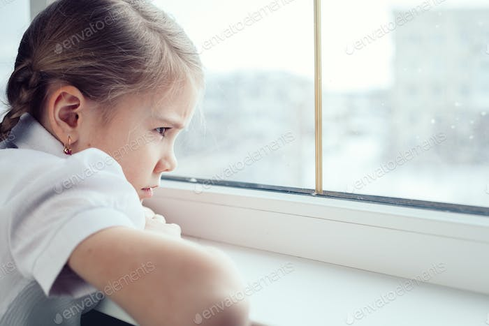 sad little girl sitting near the window