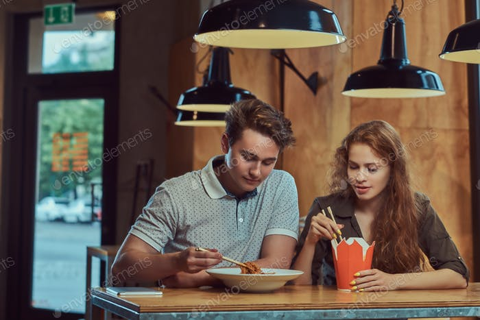 Junge Paare Studenten sitzen am Tisch in der College-Kantine während einer Pause.