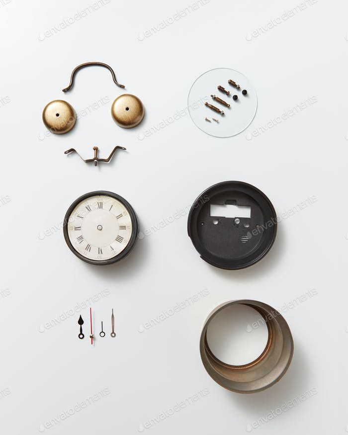 Different details of an old mechanical clock and a smiling face made from details on a gray