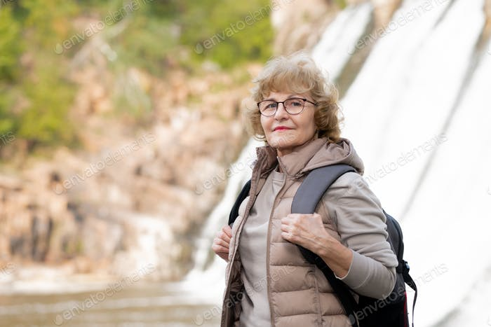 Happy mature female tourist in activewear and eyeglasses