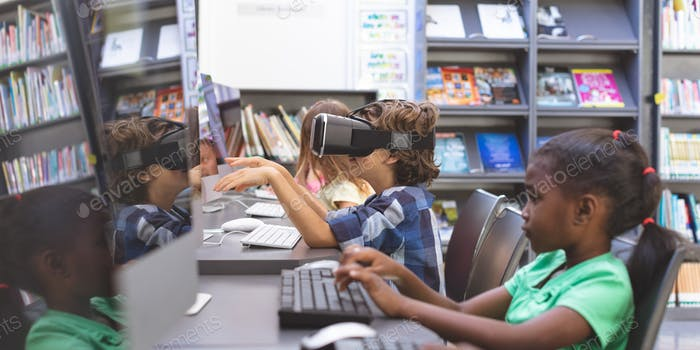 Schoolboy using virtual reality headset while schoolgirl working on computer in computer room