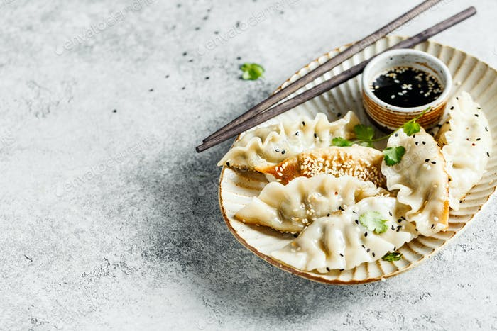Fried dumplings Gyoza on a ceramic plate with soy sauce and sesame