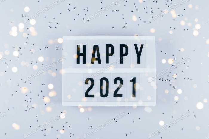 Happy New Year 2021 celebration. Light box with text Happy 2021 and sparkles on grey background