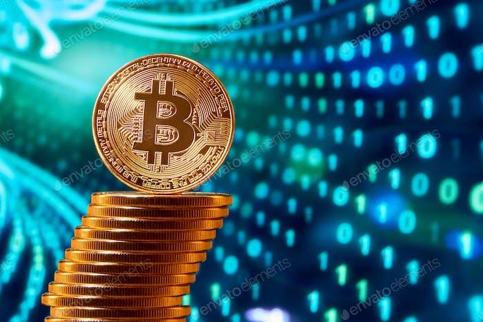 Pila de bitcoins dorados con un bitcoin en su borde colocado sobre fondo azul borroso