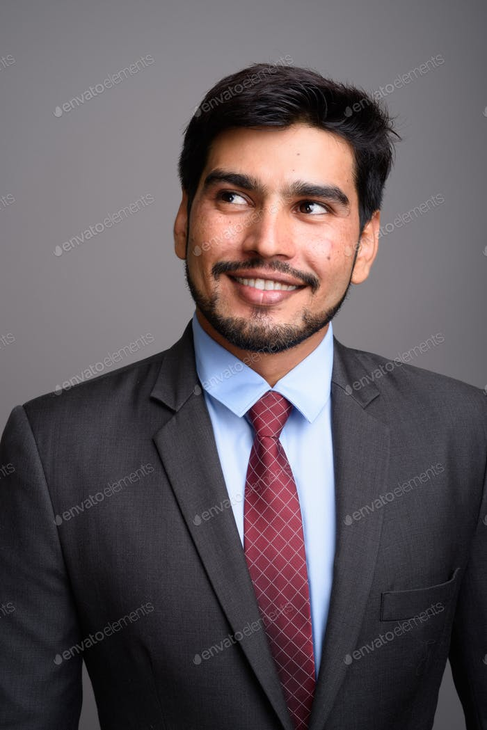Young handsome bearded Persian businessman against gray backgrou