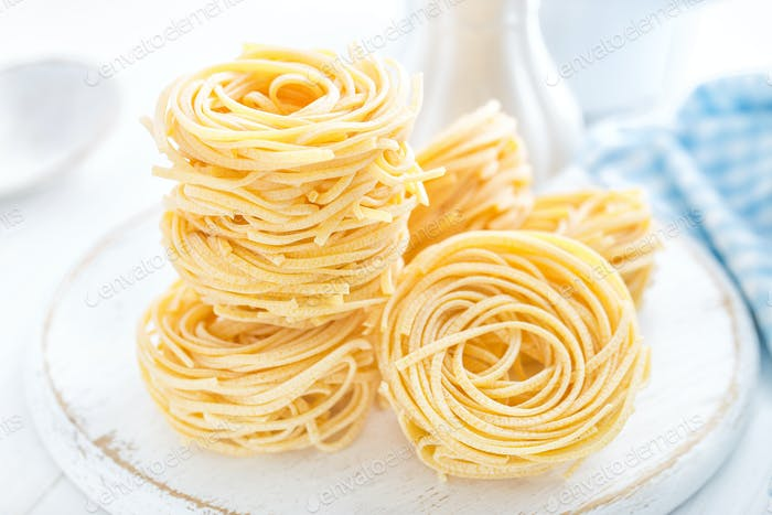 Raw pasta on white background closeup