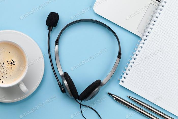 Büroschreibtisch mit Headset und Laptop. Von zu Hause aus arbeiten