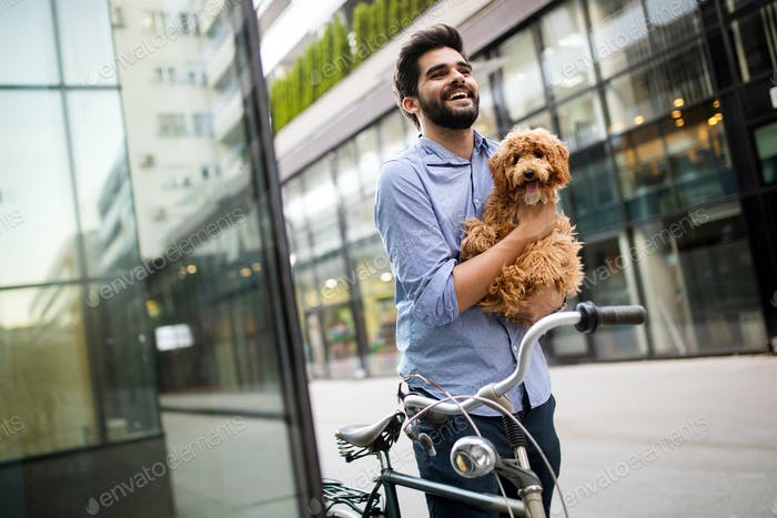 Handsome young businessman walking with his lovely dog