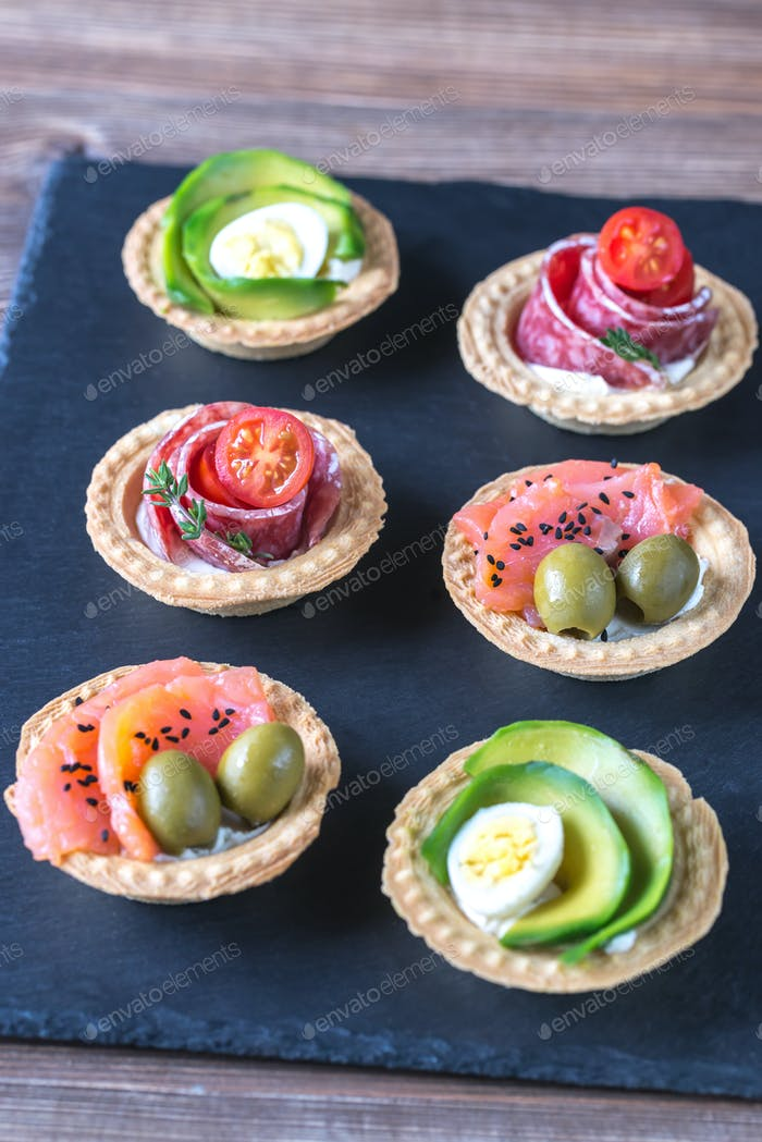 Tartlets with different fillings on the stone board