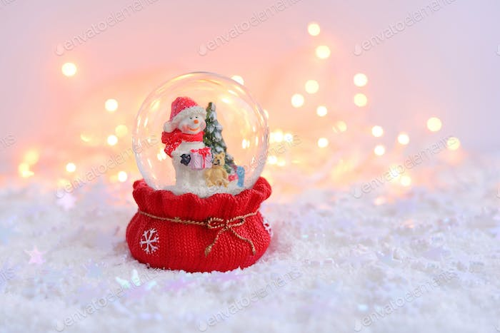 A snow globe with snowman on snow and Christmas lights. A Festiv
