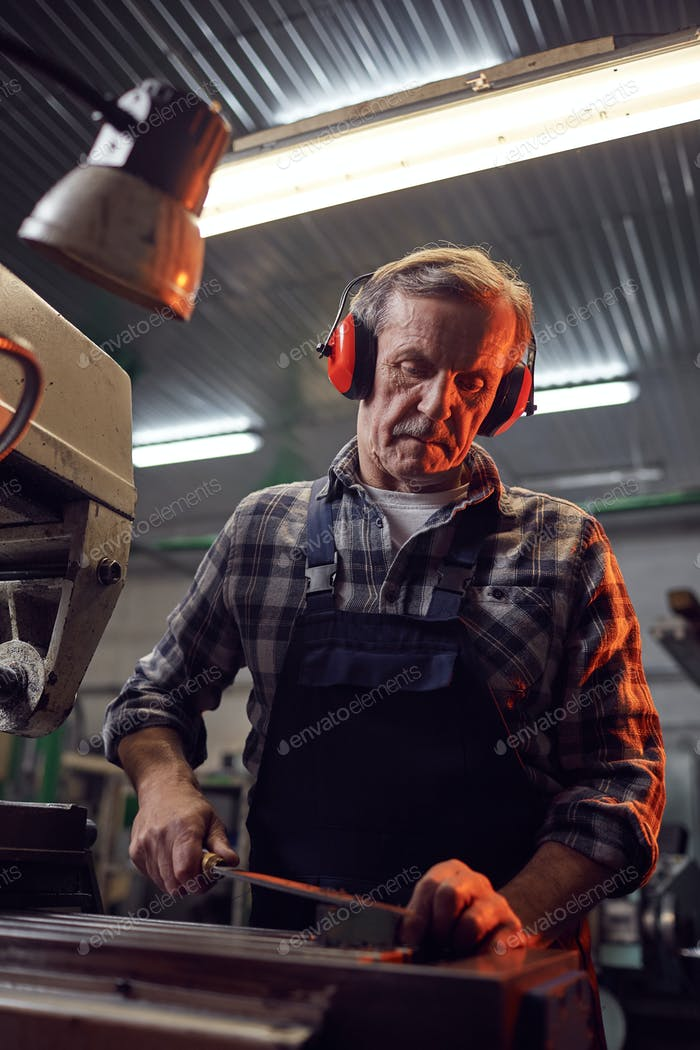Worker sawing the metal