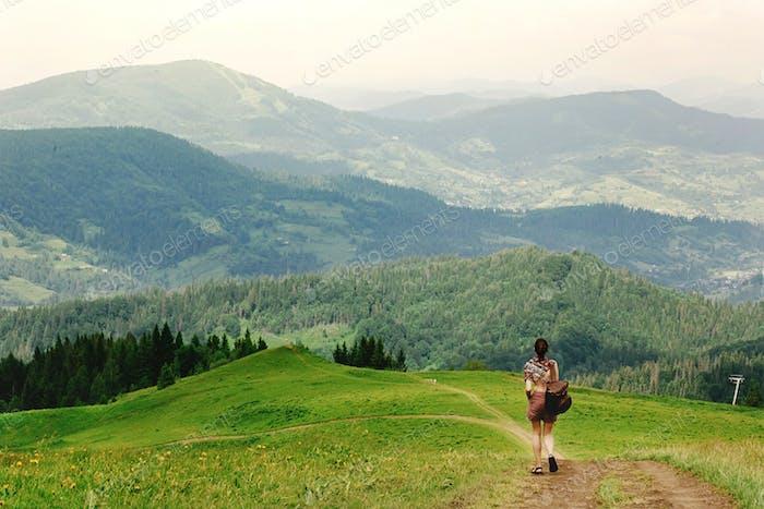 stylish hipster traveler walking at amazing mountains