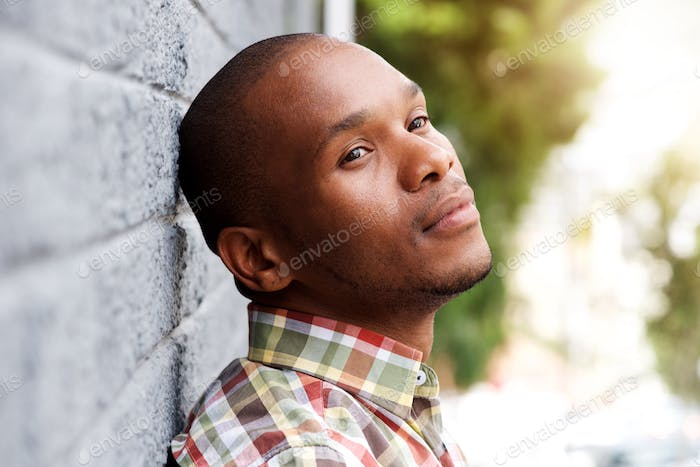 young man leaning against wall and thinking