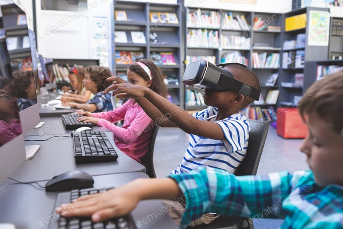 Schoolboy using virtual reality headset while his schoolmaes working on computer in computer room