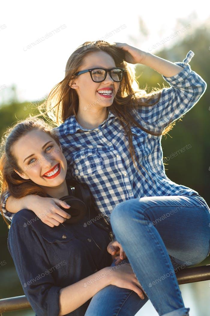 zwei verspielte Mädchen mit Spaß im freien bei Sonnenuntergang Licht