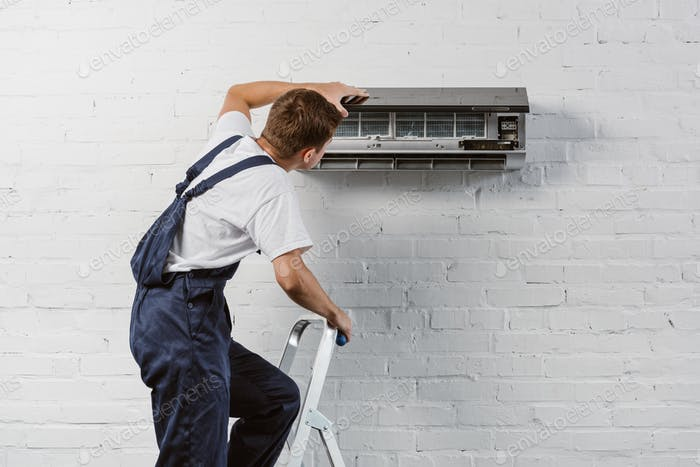 rear view of air conditioner repairman standing on stepladder