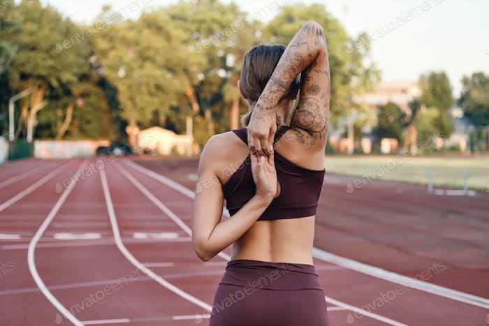 Athlete girl in sportswear holding hands behind back training on city stadium