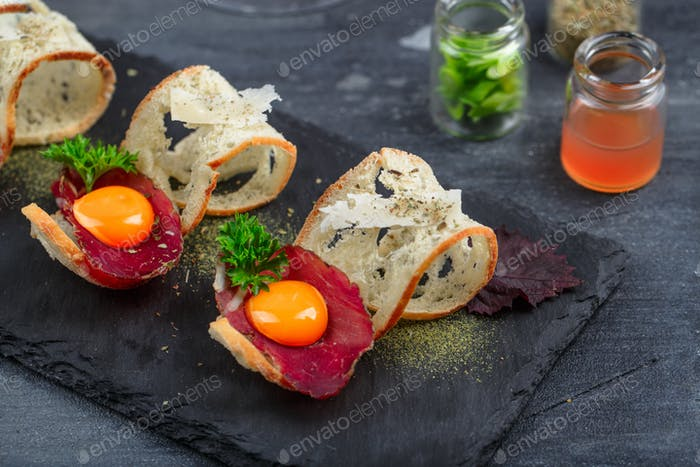 Cured beef on crusty bread with yolk and parmedgano cheese