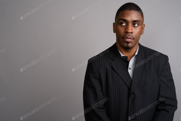 Young handsome African businessman wearing suit against gray bac