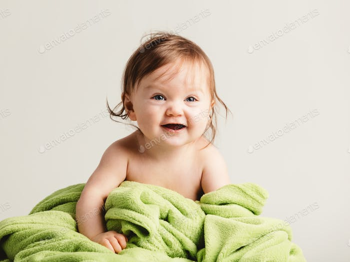 Cute baby girl with cozy green blanket smiling.